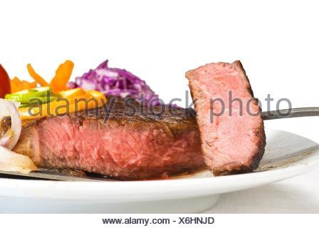 fresh juicy beef ribeye steak sliced ,with lemon and orange peel on top and vegetable beside. - Stock Photo
