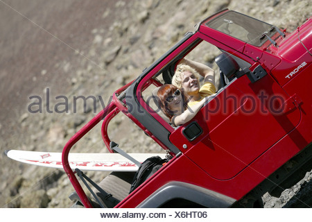 young couple on vacation with jeep and surfboard, Spain, Canary, Lanzarote - Stock Photo