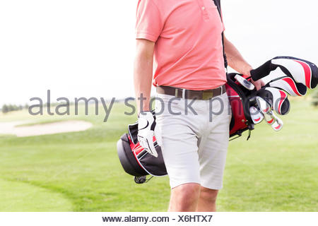 Midsection of man with golf club bag standing at course - Stock Photo