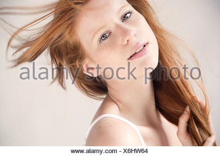 Young woman with hair blowing in breeze, portrait - Stock Photo