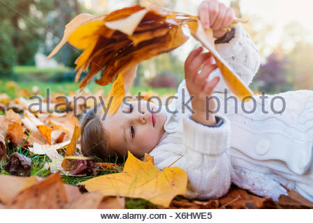 Girl lying in autumnal meadow holding leaves - Stock Photo