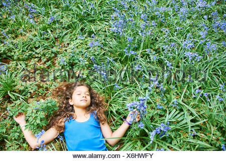 Girl laying in field of flowers - Stock Photo