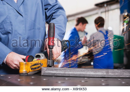 Germany, Neukirch, Person using grinder,  Apprentice and foreman in background - Stock Photo