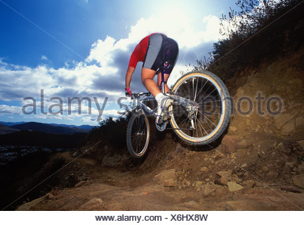 A mountain biker jumping down a hill on a singletrack trail - Stock Photo