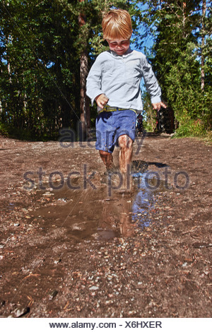 Young boy splashing in muddy puddle - Stock Photo
