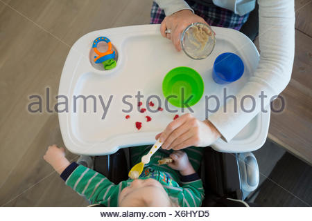 Overhead view mother feeding baby boy high chair - Stock Photo