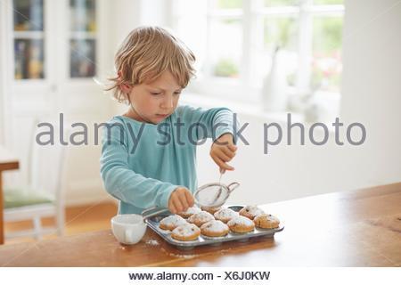 Boy making cupcakes in kitchen - Stock Photo