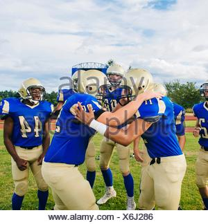 Teenage and young male American football players congratulating each other on soccer pitch - Stock Photo