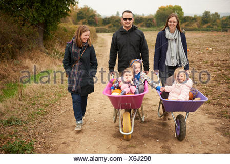 Portrait of parents pushing three girls in wheelbarrows along pumpkin field - Stock Photo