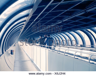 Visitors to the fair on a moving walkway in a connection corridor, Messe Duesseldorf fair hall, Duesseldorf - Stock Photo