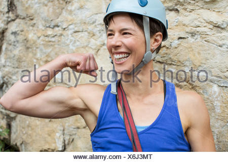 female rock climber showing off muscles - Stock Photo