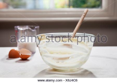 Empty mixing bowl, eggshells and milk - Stock Photo