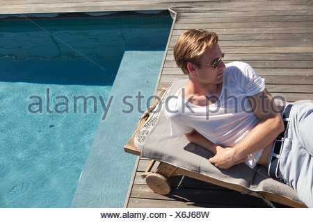 Man relaxing by swimming pool - Stock Photo