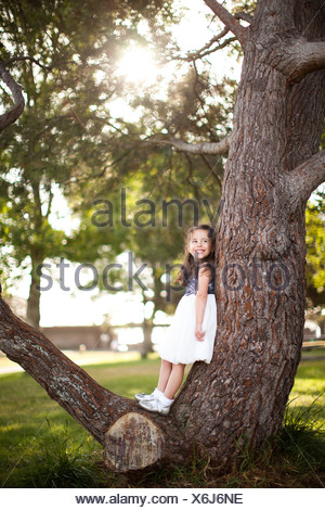 Portrait of girl standing on tree trunk - Stock Photo