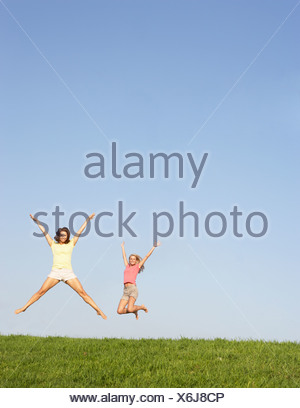 Two young couples, pose together, in park - Stock Photo