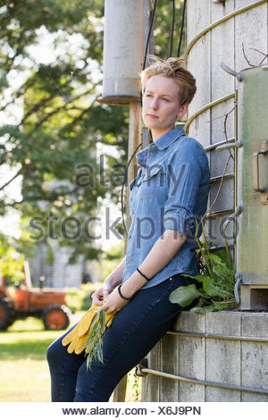 Young woman on a working farm, taking a break in the shade of a silo. - Stock Photo