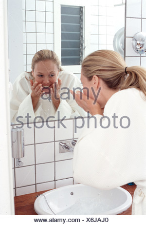 Back view of female long wavy blonde hair in ponytail wearing white dressing gown splashing water onto face over sink looking - Stock Photo