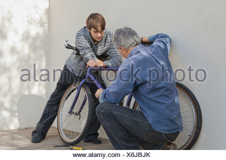 Father helping son repair bicycle - Stock Photo