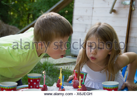 Brother and sister blowing out birthday candles - Stock Photo