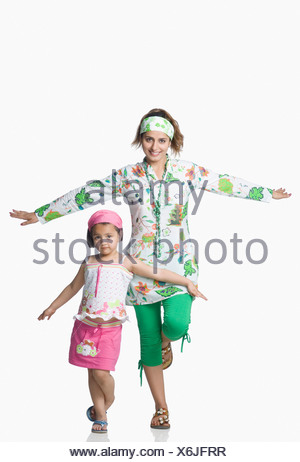Portrait of a young woman and her daughter standing with their arms outstretched - Stock Photo