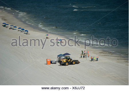 Workers clean up oil on the beach from the British Petroleum oil spill. - Stock Photo