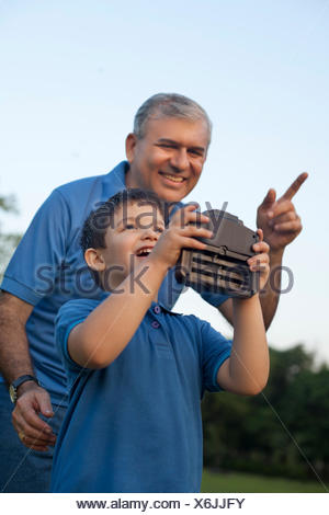 Grandfather and Boy Playing with Radio Controlled Handset - Stock Photo