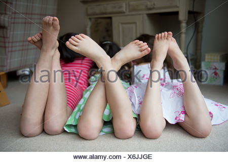 Girls lying on floor together with feet up - Stock Photo