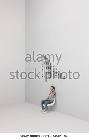 Man listening to MP3 player with headphones, CD cases arranged in pattern on wall - Stock Photo