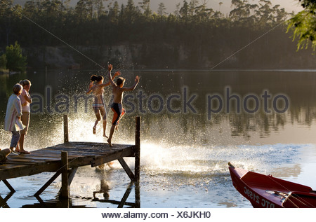 Multi generational family standing on jetty at sunset children 7 10 jumping into lake side view - Stock Photo