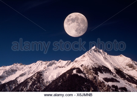 View from Mt. Ginzling aka Boeckenberg onto the full moon hanging over Mts. Dristner, Blaser and Roflspitze, Zillertal Alps, Ti - Stock Photo