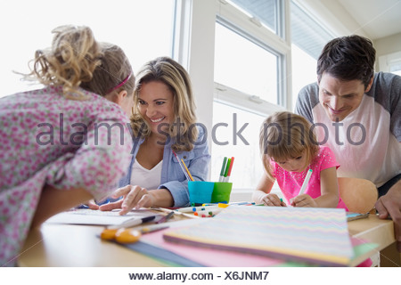 Family making paper crafts at table - Stock Photo