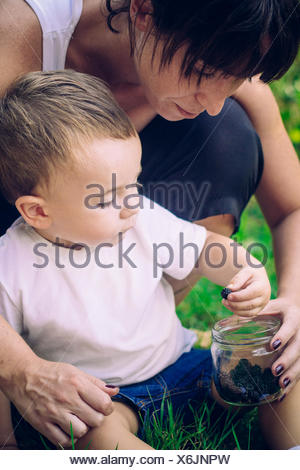 Mother giving blackberries to her son - Stock Photo