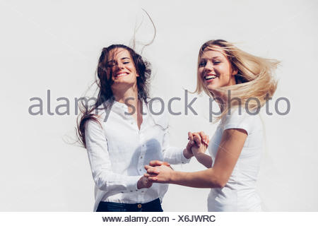Two young women holding hands tossing her hair in front of white background - Stock Photo