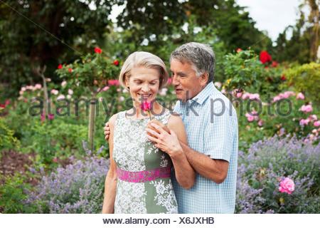 Mature man gives woman a rose - Stock Photo