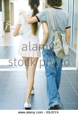 Teen couple walking in school hallway, rear view - Stock Photo
