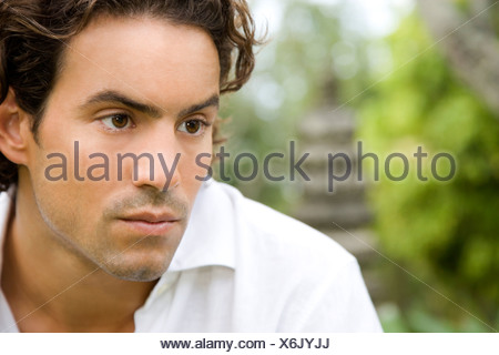 Portrait man looking serious in a tropical garden. - Stock Photo