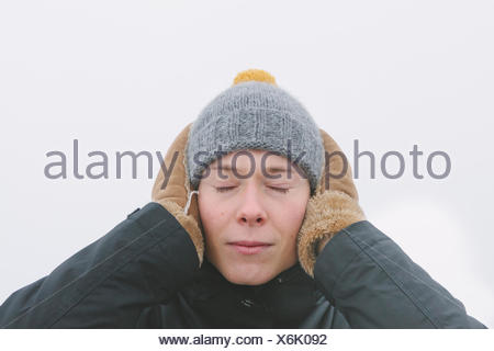 Finland, Helsingfors, Portrait of young man with eyes closed, covering ears with palms - Stock Photo