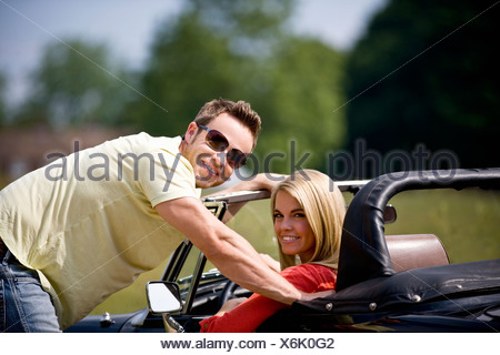 A young man standing next to a young woman in a black sports car - Stock Photo