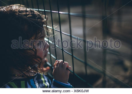 Serious boy behind fence - Stock Photo