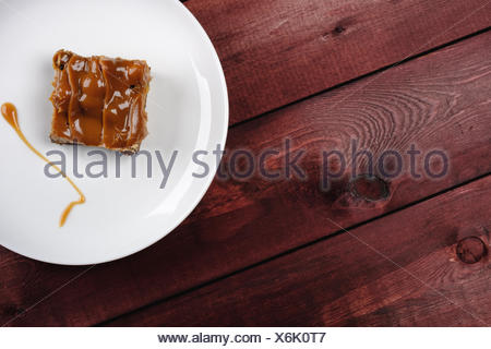 a piece of chocolate brownie and caramel sauce on a white plate. Top view - Stock Photo