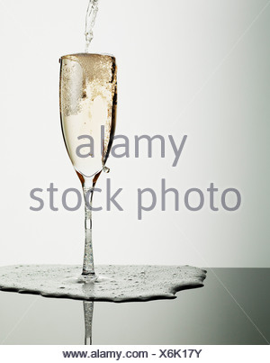 Champagne pouring into glass and overflowing - Stock Photo