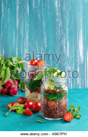 Salads with quinoa, couscous, spinach, radish, tomatoes and zucchini in glass mason jars, standing with fresh vegetables over bright turquoise wooden - Stock Photo