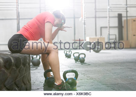 Exhausted woman sitting on tire in crossfit gym - Stock Photo
