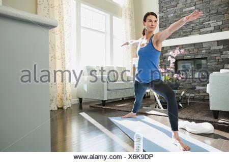 Mature woman stretching on yoga mat - Stock Photo