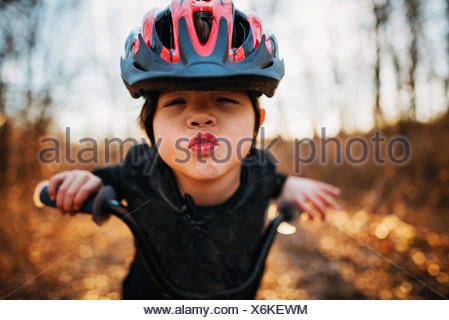 Boy on a bicycle wearing a helmet puckering lips - Stock Photo