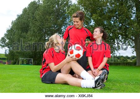 Teenage girls in soccer uniforms sitting on field - Stock Photo