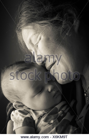 Portrait of grandmother holding baby granddaughter - Stock Photo