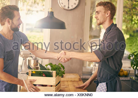Chef and vegetable delivery man shaking hands - Stock Photo