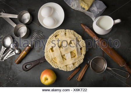 Not baked apple pie with Ingredients for baking. Milk, eggs, butter, flour - Stock Photo