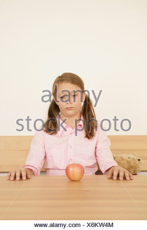 Girl 10 13 looking at apple - Stock Photo